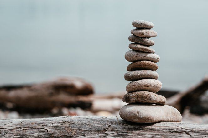 rock-stack-on-log-by-water